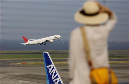 Woman watches a JAL aeroplane taking off behind an ANA aeroplane at Haneda airport in Tokyo